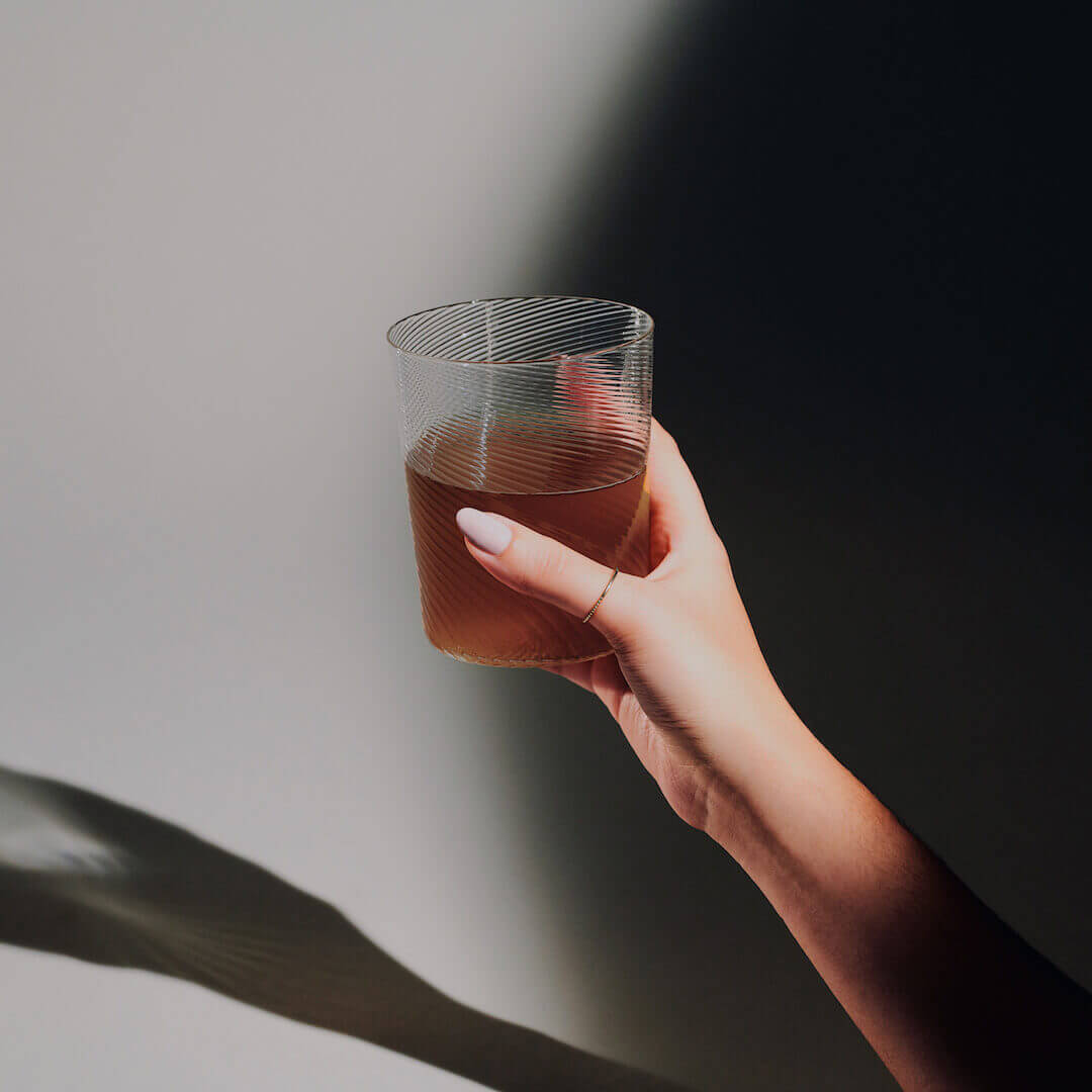 Hand with a glass of Calm